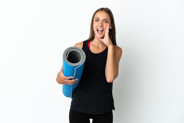 口を大きく開いて叫んで孤立した白い背景の上にマットを保持しながらヨガのクラスに行くスポーツの女性