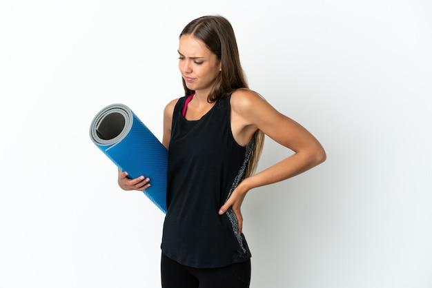 努力したために腰痛に苦しんでいる孤立した白い背景の上にマットを保持しながらヨガのクラスに行くスポーツの女性