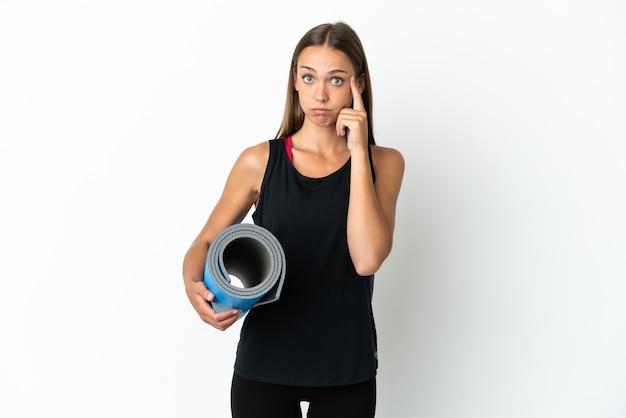 아이디어를 생각하는 격리 된 흰색 배경 위에 매트를 들고 요가 수업에가는 스포츠 여자