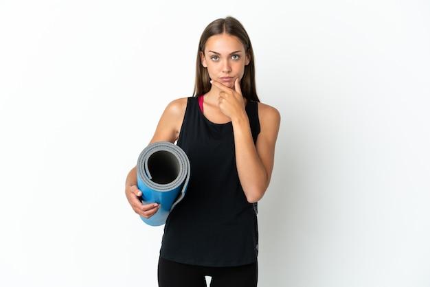 孤立した白い背景の思考の上にマットを保持しながらヨガのクラスに行くスポーツの女性