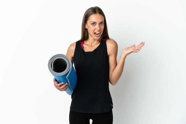 충격 된 표정으로 격리 된 흰색 배경 위에 매트를 들고 요가 수업에가는 스포츠 여자