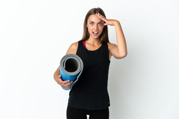 놀람 표정으로 격리 된 흰색 배경 위에 매트를 들고 요가 수업에가는 스포츠 여자