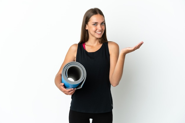 Sport woman going to yoga classes while holding a mat over isolated white background extending hands to the side for inviting to come