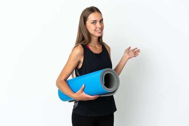 Sport woman going to yoga classes while holding a mat isolated