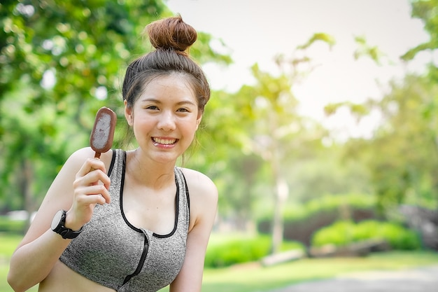 Sport woman holding ice cream in hands on summer