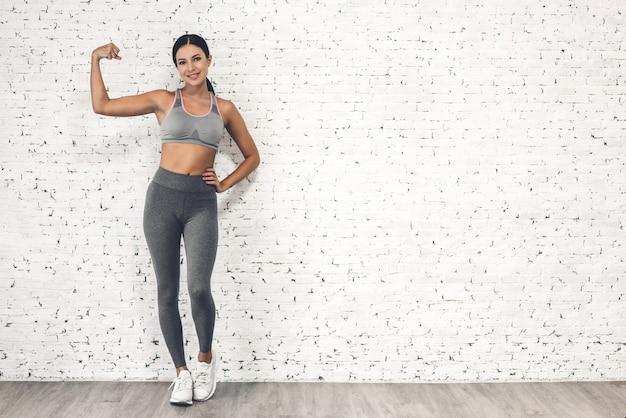 Спортивная женщина в спортивной одежде расслабляется после тренировки против места для копирования для добавления текста с белой стеной