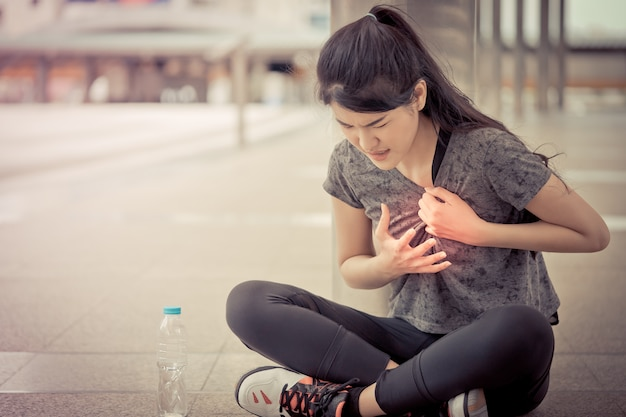 Sport woman is having an injury on her heart chest disease attack
