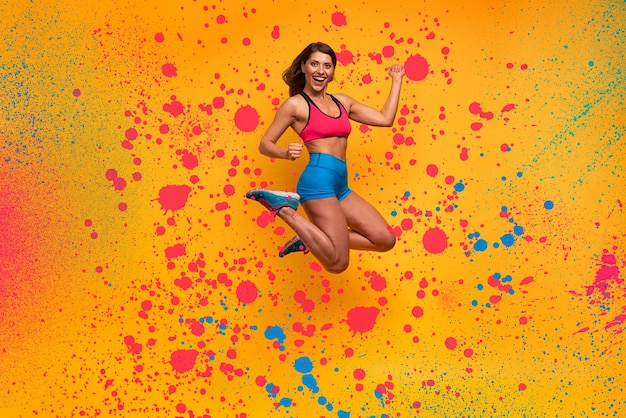 スポーツの女性がジャンプします。幸せで楽しい表情。スプレー効果