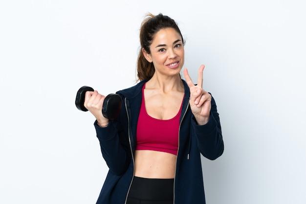 Женщина спорта делая поднятие тяжестей над изолированной белизной усмехаясь и показывая знак победы