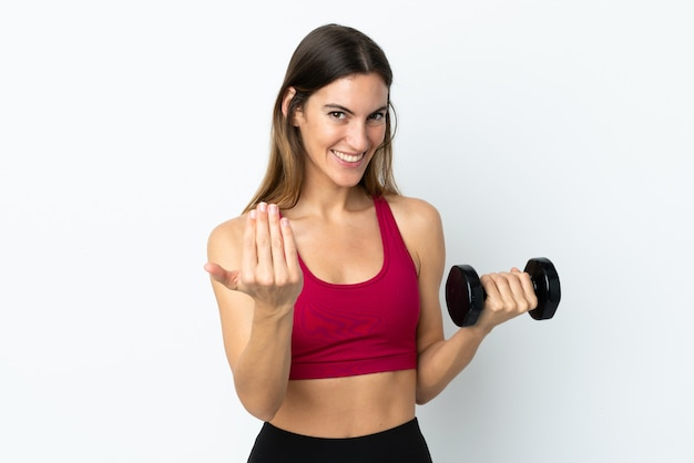 Sport woman making weightlifting on white wall inviting to come with hand.