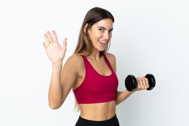 Sport woman making weightlifting on white wall saluting with hand with happy expression