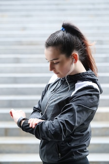 Sport woman outdoor looking her wristwatch