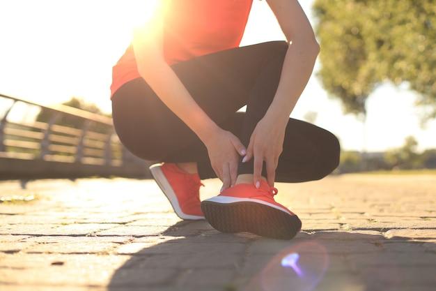 スポーツの女性-痛みを伴う捻挫した足首を痛みで抱えているランナー。関節や筋肉の痛みがあり、下半身に痛みを感じる女性アスリート。