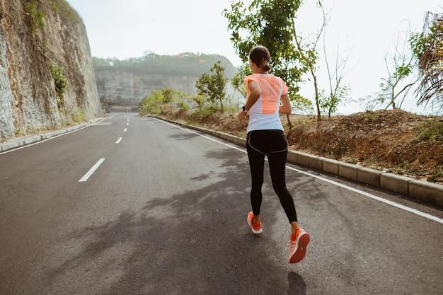 Спорт женщина работает на обочине дороги