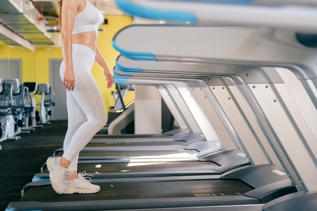 Sport woman running on treadmill in gym, keeps fit, burn calories on running machine, wearing white sportswear and sneakers.