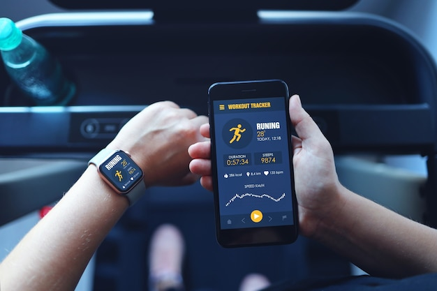 러닝머신을 달리는 스포츠 여성은 스마트워치를 사용하여 스마트폰 운동 앱과 음악 듣기를 연결합니다. 실내 체육관 배경입니다. 건강 스포츠 개념