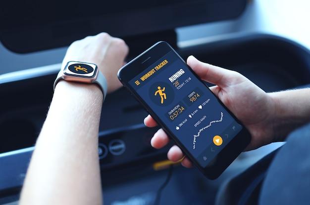 Спортивная женщина, бегущая на беговой дорожке, использует умные часы, подключает приложение для тренировки смартфона и слушает музыку. фон в помещении тренажерный зал. концепция здоровья спорта