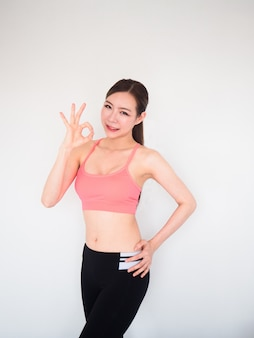 Sport woman show ok sign with finger and posing on white background,fitness concept