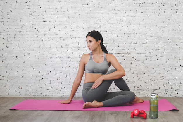Sport woman sitting relax on pink mat and do fitness exercise with water bottle at home.diet concept.fitness and healthy lifestyle