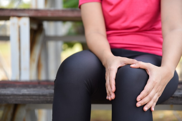 Sport woman suffering from running knee during outdoor workout and sitting at the bleachers.