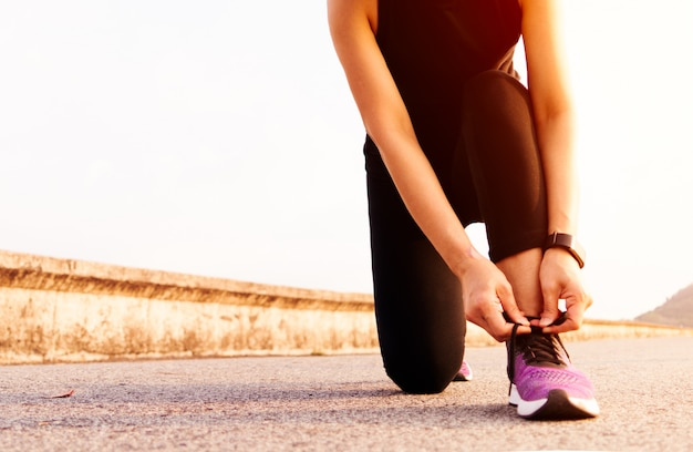 Sport woman tying shoelace while running, sunset on the long road