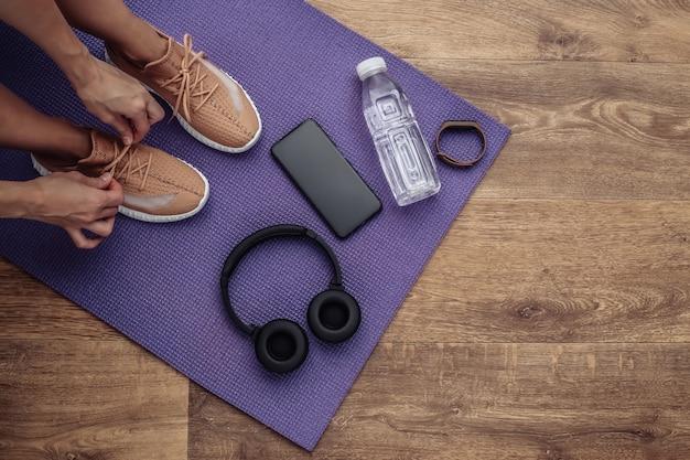 敷物の上に座っている間靴ひもを結ぶスポーツの女性。健康的なライフスタイルのコンセプト。上面図