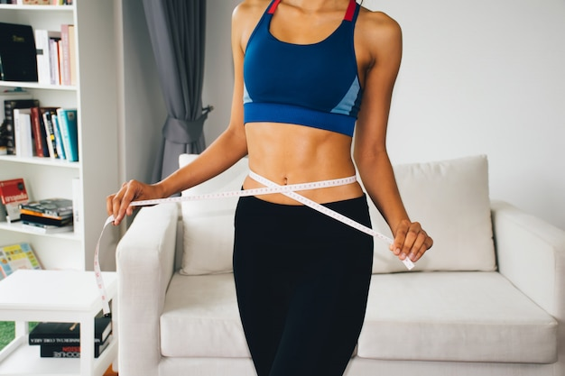 Sport woman using measuring tape on body.