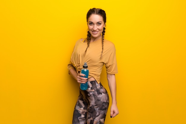 Sport woman on vibrant yellow background with a bottle
