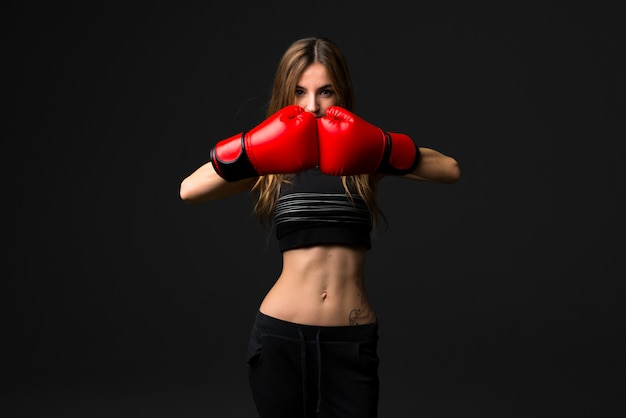 Sport woman with boxing gloves on dark background