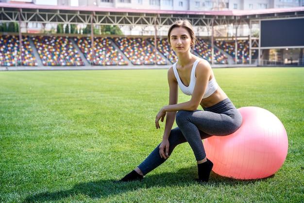 緑の芝生の上で屋外でエクササイズフィットボールとスポーツの女性