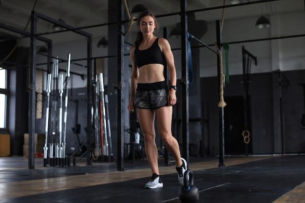 ジムでケトルベルを持つスポーツの女性。