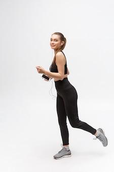 スポーツの女性。音楽を聴いてスポーツ服を着た若い美しい女性。
