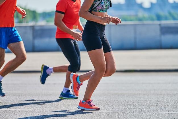 Спортивные женщины бегают в спортивной одежде на городской дороге