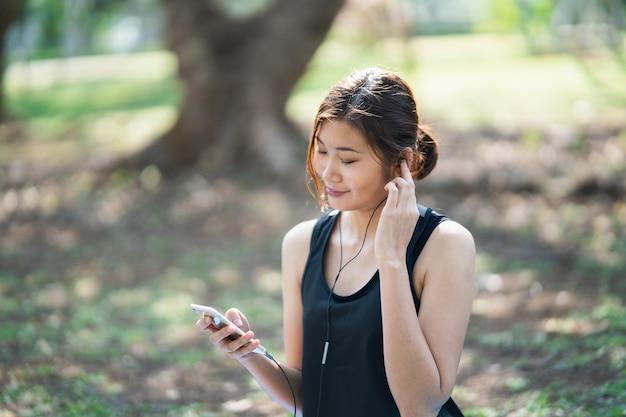공원에서 이어폰으로 음악을 듣고 스포츠 여성