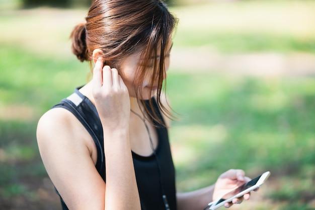 Sport women listening music with earphones in the park