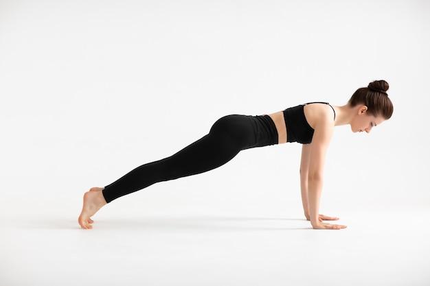 스포츠, 요가, 사람 개념, 판자를 하고 균형을 잡는 젊은 여성. 스포티한 여성의 전신 프로필 사진은 플랭크 운동을 근육질의 건강한 사람으로 만들고 싶어합니다. 흰색에 격리.