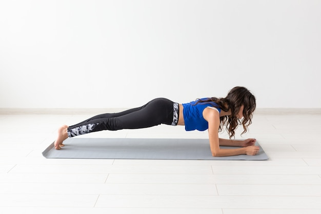 Sport, yoga, people concept - a young woman is doing a plank, yoga, taking a balance.