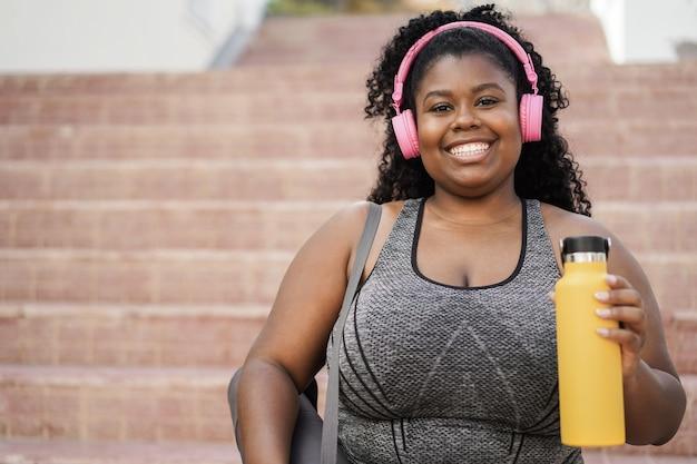 Спортивная молодая африканская женщина слушает музыку с наушниками - фокус на лице