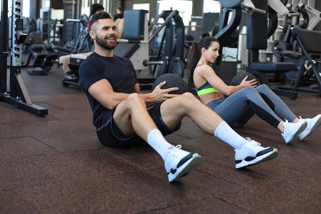 腹筋運動セッション中に薬のボールと一緒に運動している体育館の床に座っているスポーツの若者。