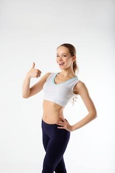 完璧なボディを持つスポーツ若い女性はokのしぐさ、フィットネスを表示します。