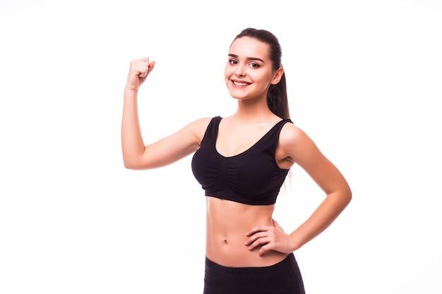 上腕二頭筋を示す完璧なボディを持つスポーツの若い女性、白い背景の上に撮影されたフィットネスの女の子のスタジオ
