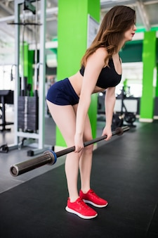 Sportclubでファッションスポーツウェアのバーベルで演習を行う若い女性