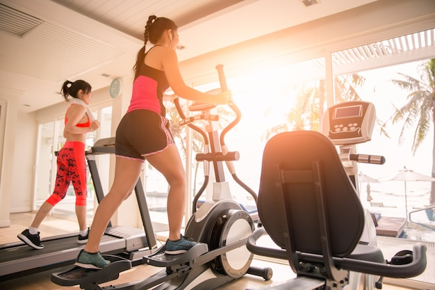 Sportgirl exercise on elliptical cross trainer and treadmill at gym