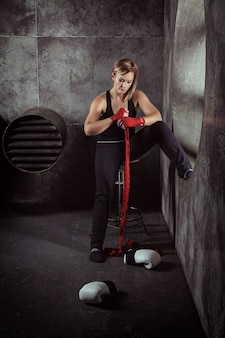 Sporting blonde woman in boxing bandages and boxing gloves around in dark studio