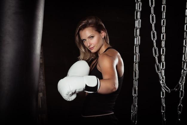 Sporting blonde woman in boxing gloves in dark studio looking at camera