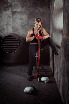 暗いスタジオでボクシングの包帯とボクシンググローブでスポーツ金髪の女性