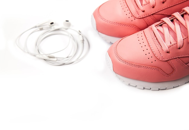 Sporting pink sneakers on a white with headphones. training.