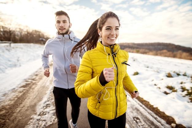 雪に覆われた道路で冬の日に実行されている陽気なアクティブな友人。