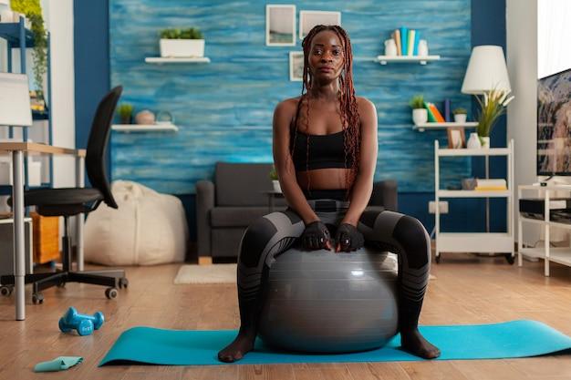 Donna forte e attiva sportiva seduta su una palla di stabilità che riposa, dopo un intenso allenamento nel soggiorno di casa