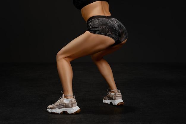 Спортивные и мускулистые ноги фитнес-инструктора, делающего приседания на черном фоне